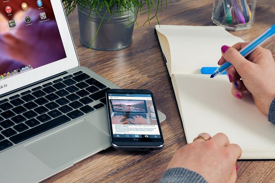 Laptop, telefon, kobieta pisząca w notesie. Lokowanie produktu na blogu i vlogu.